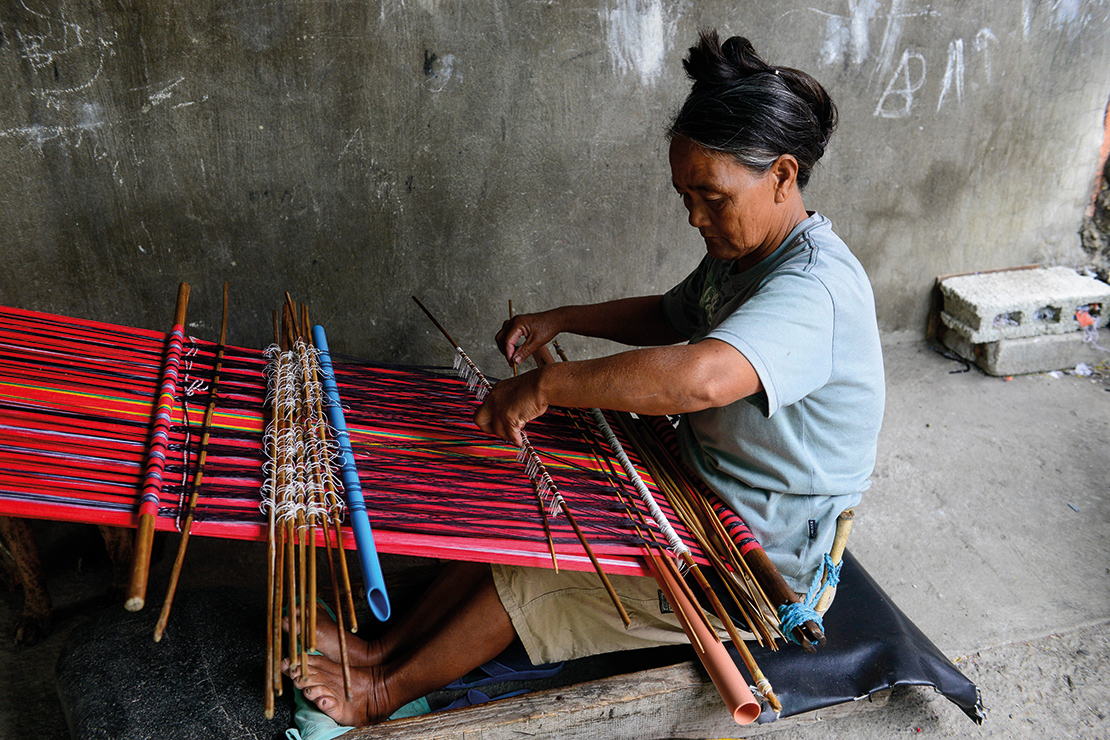 A woman works on a loom in Bontoc. Traditional crafts like weaving are being shared with new generations through initiatives organised by Partners for Indigenous Knowledge Philippines, and other organisations. Credit: Joerg Boethling.