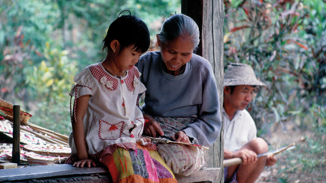 An indigenous Shan woman teaches her granddaughter how to make a bamboo fan near Hsipaw, Shan State, Myanmar. Credit: Ray Waddington.