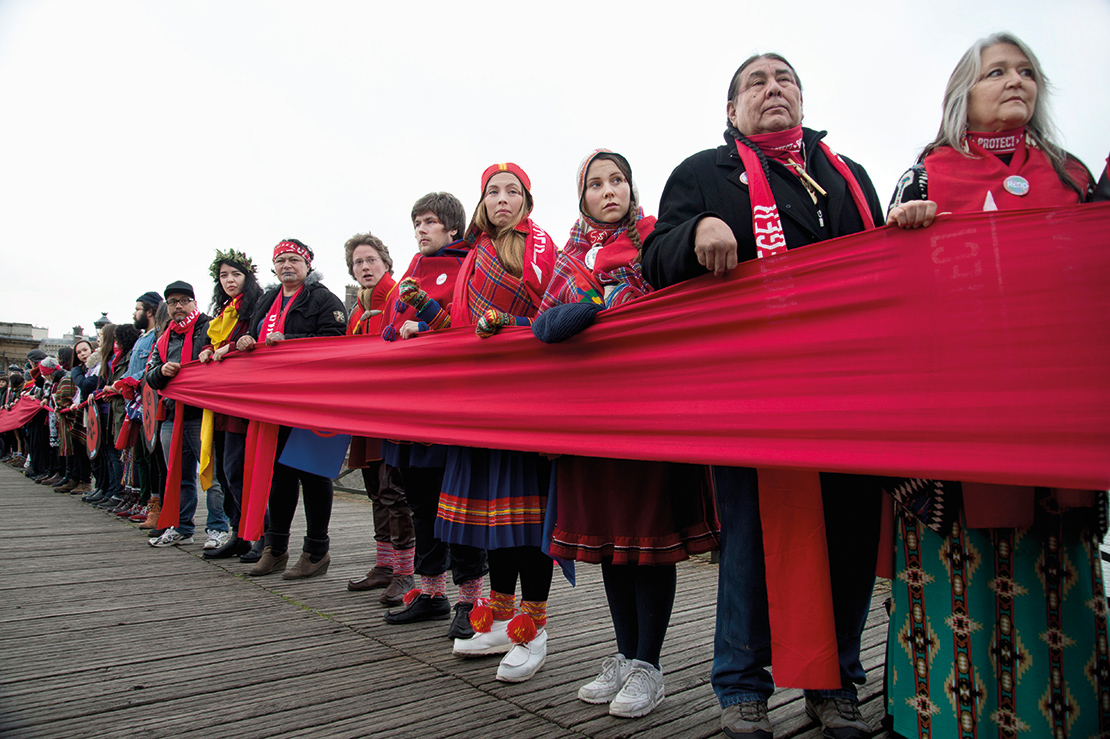 Indigenous activists holding a 'Red Line' on the Pont des Arts during the COP 21 UN Climate Conference in Paris, France. IPLCs are participating actively in policy forums and global climate change initiatives. Credit: Jenny Matthews.