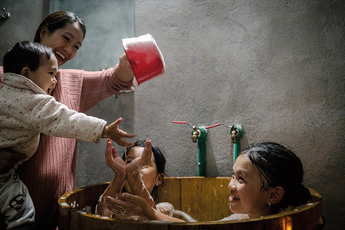 A family taking a herbal bath. The bath is prepared by boiling leaves, plants and tree bark to create a traditional bath with medicinal properties and a pleasant aroma. The stem of black cardamom (thao qua) is also used in the preparation. Credit: Ian Teh.